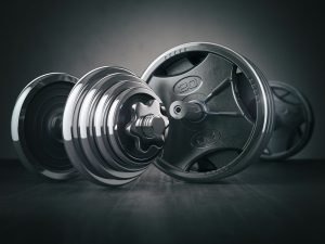 Barbell and dumbell. Sports bodybuilding equipment on black back