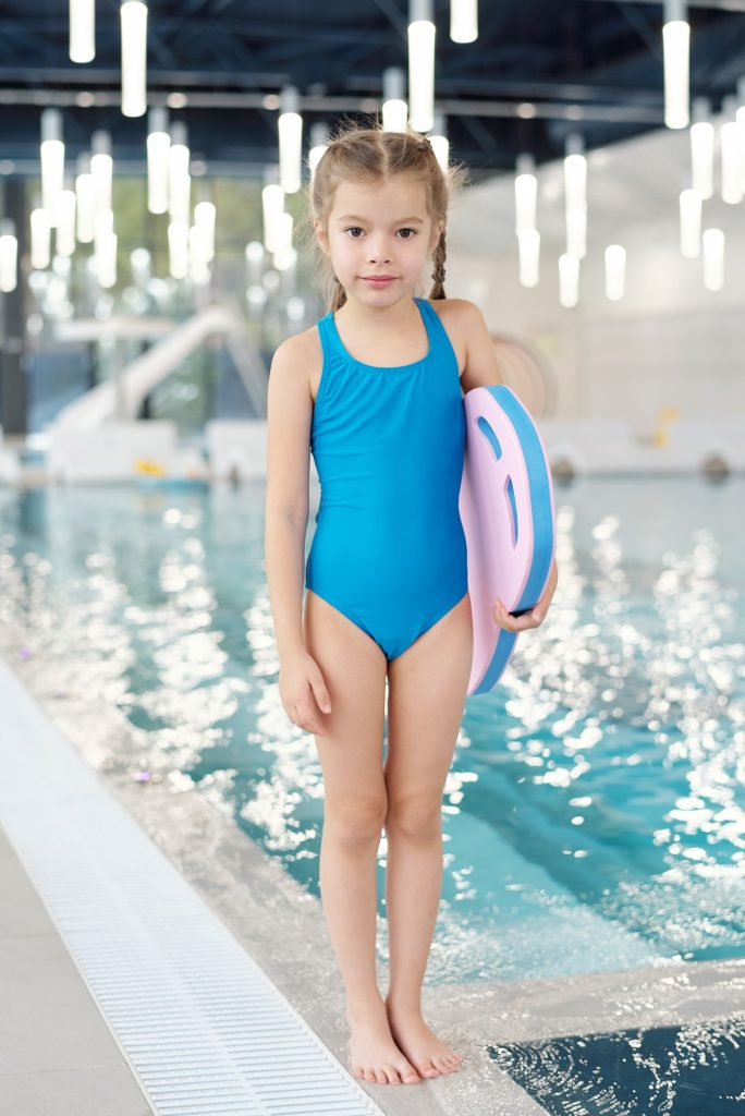 Pretty child with swimming board standing against poolside in sports center