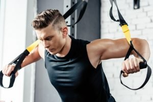 young muscular sportsman training with trx resistance bands in gym