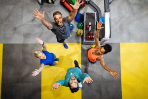 Fitness, sport, training, gym, success and lifestyle concept. Group of happy friends in the gym