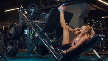 Beautiful fitness woman in sportswear doing exercise on the legs press machine in the gym.